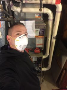masked hvac technician posing with furnace after furnace installation